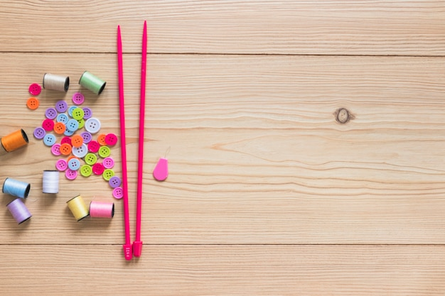 Colorful button and spool with pink knitting needles on wooden backdrop Free Photo