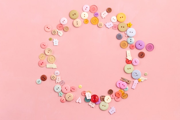 Colorful buttons on pink. flat lay, sewing concept. rounded frame composition Premium Photo