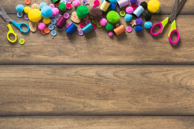 Colorful buttons; spool; scissor and cotton balls on wooden table with space for text Free Photo