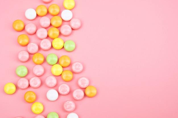 ピンクに分離されたカラフルなキャンディー Premium写真