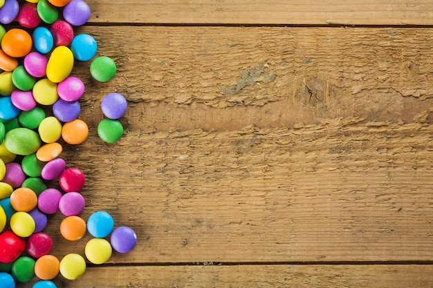 Colorful candies on wooden background Free Photo