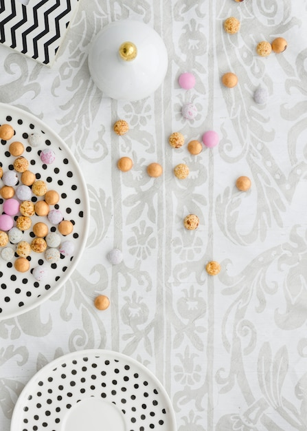 Colorful candies on polkadot plates over the floral tablecloth Free Photo