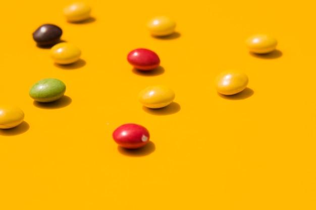 Colorful candies on yellow backdrop Free Photo