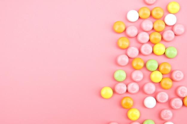 ピンクの背景にカラフルなキャンディ Premium写真