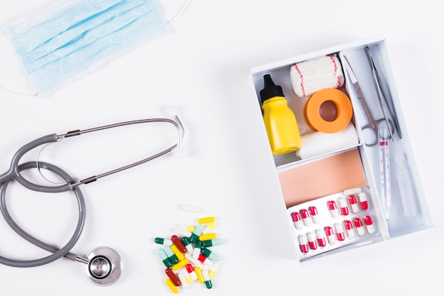 Colorful capsules; stethoscope and mask with first aid kits on white background Free Photo