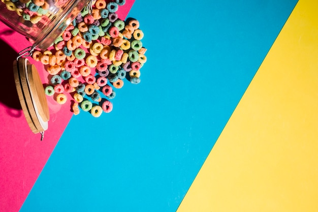 Colorful cereal loop rings spilling from jar on colorful backdrop Free Photo