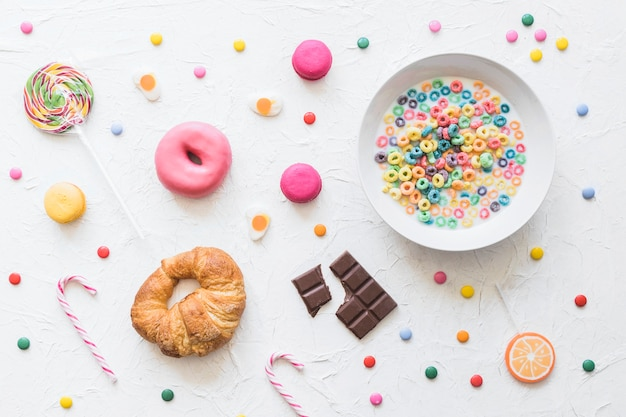 Colorful cereal in milk bowl over the sweet food on textured backdrop Free Photo