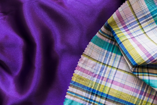 Colorful chequered pattern cloth on plain purple textile Free Photo