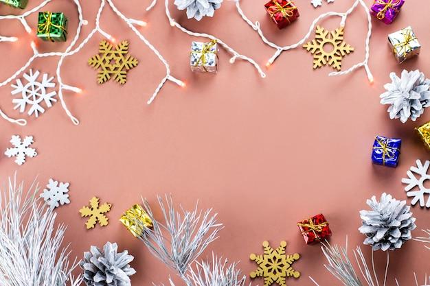 Красочная новогодняя рамка со снежинками, подарками и рождественскими огнями на теплом коричневом фоне Premium Фотографии