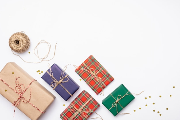 Colorful christmas presents with golden stars and string Free Photo