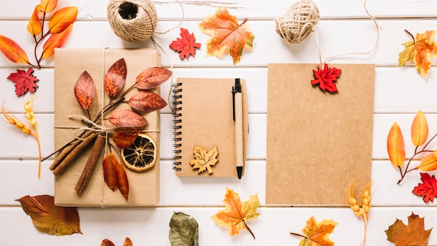 Colorful composition with autumn leaves, gift and notebook Free Photo