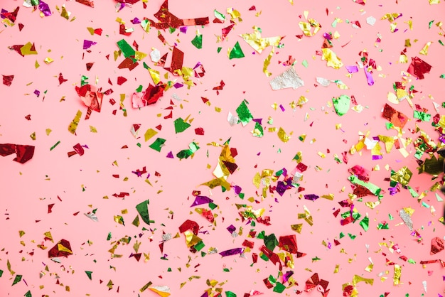 Colorful confetti on pink background Free Photo