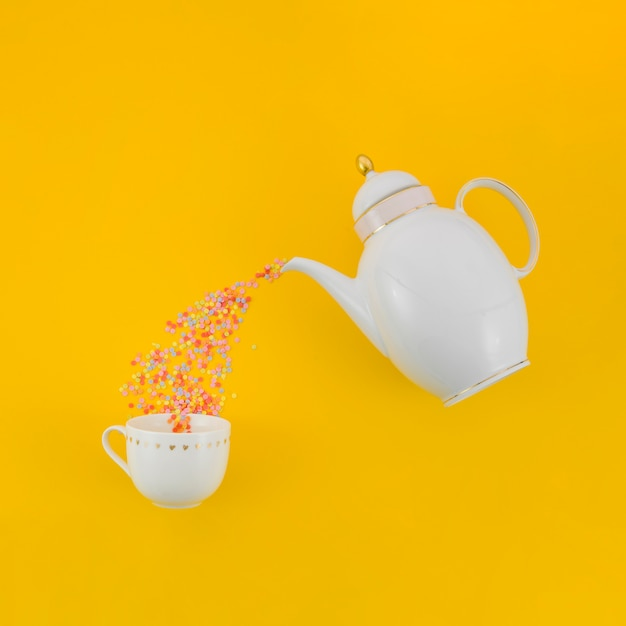Colorful confetti pouring from white tea pot in the ceramic cup against yellow background Free Photo