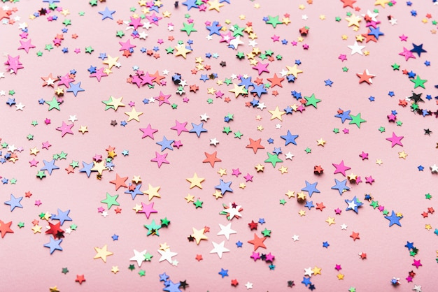 Colorful confetti stars on pink background Free Photo