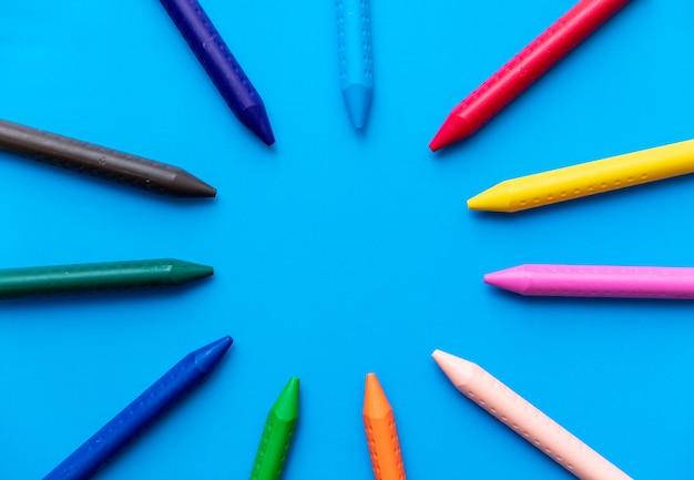Pastelli colourful che formano una vista superiore del cerchio su un ciano fondo Foto Gratuite