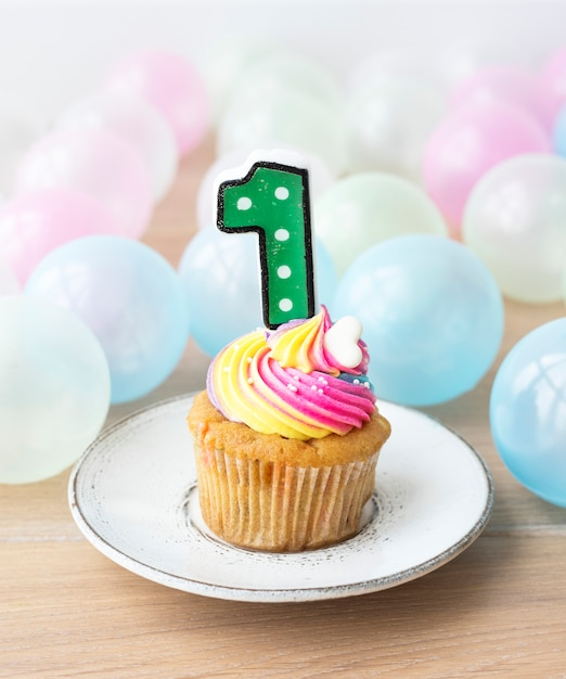 Colorful cupcake with a number one candle Free Photo