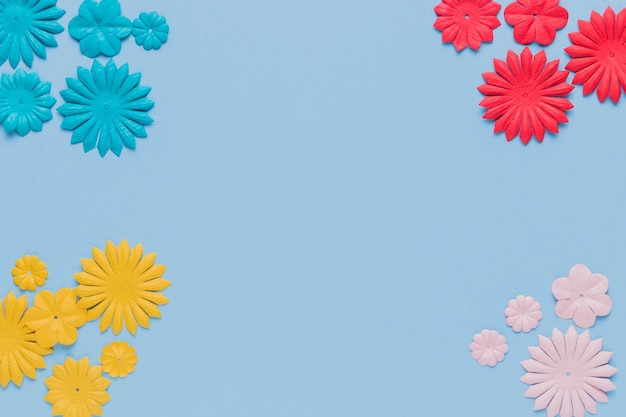 Colorful decorative flower cutout at the corner of blue background Free Photo