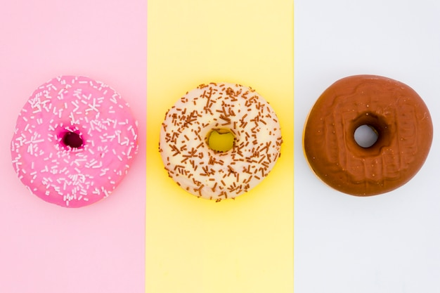 Colorful donuts on colored striped backdrop Free Photo