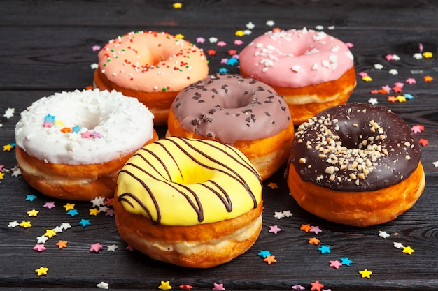 Colorful donuts decorated with confetti sprinkles on dark wooden background Premium Photo