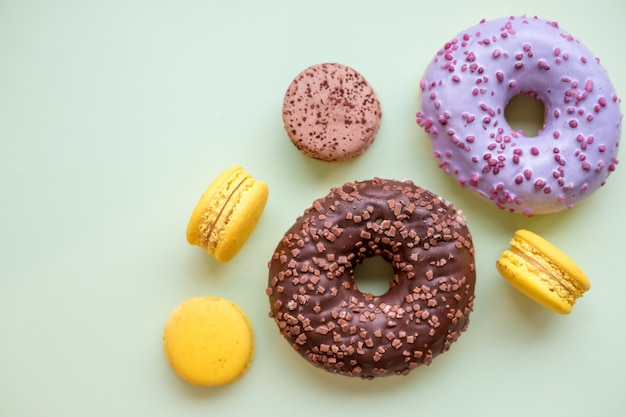 Colorful donuts and macaroons on wooden table. Premium Photo