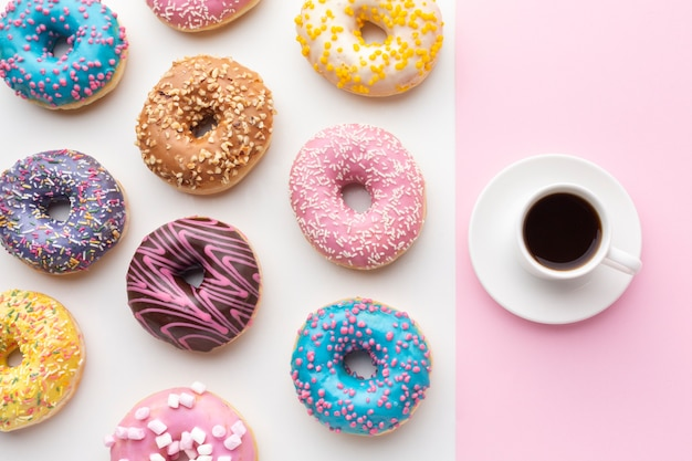 Colorful donuts with coffee top view Free Photo