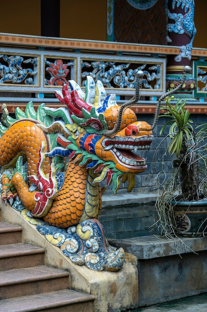Colorful dragon sculpture at the entrance to a buddhist temple on the steps in the city of danang Premium Photo