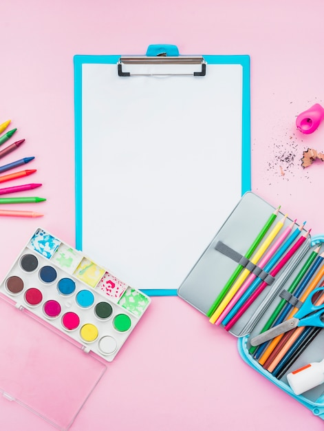Colorful drawing accessories and clipboard over the pink background Free Photo