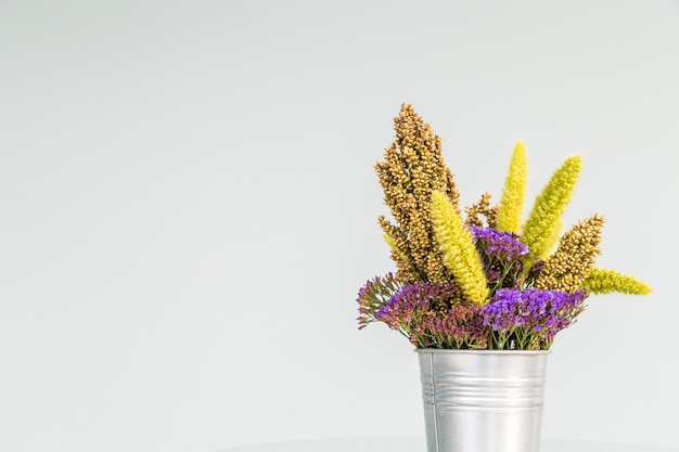 A colorful dry flower on an aluminum bucket with white background. Premium Photo