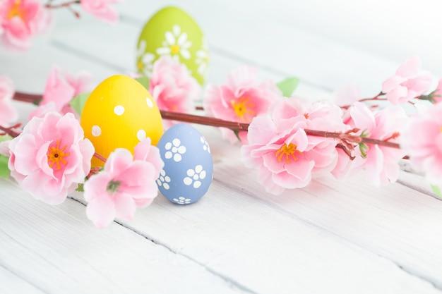 カラフルなイースターエッグと花の枝 Premium写真