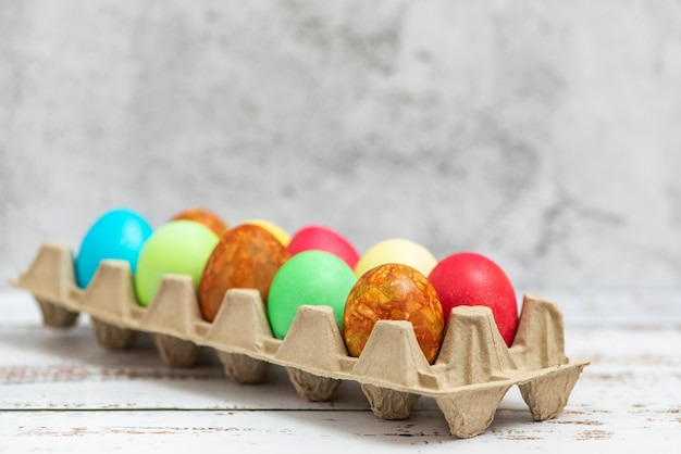 Colorful easter eggs in a cardboard egg box on light. Premium Photo