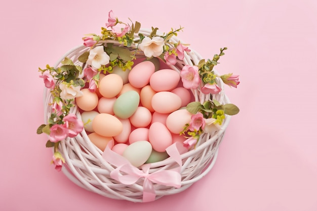 Colorful easter eggs in nest on pastel color background with flowers. Premium Photo