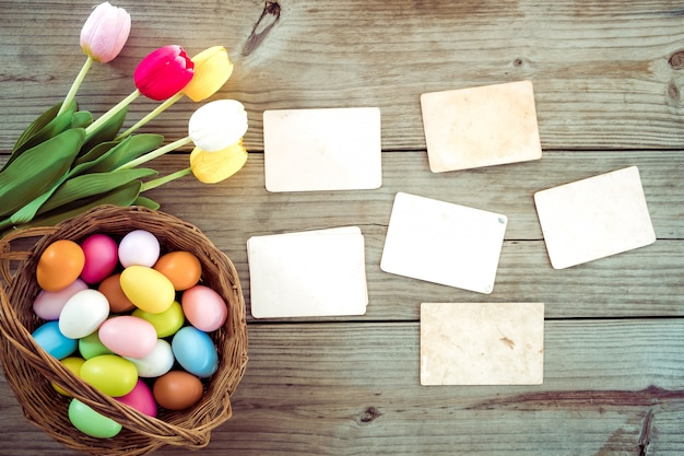 Colorful easter eggs in nest with flower and empty old paper photo album on wood table Premium Photo