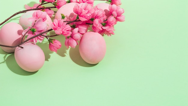 Colorful easter eggs with flowers on green table Free Photo