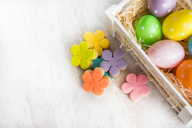 Colorful easter eggs in wooden box and homemade fondant Premium Photo