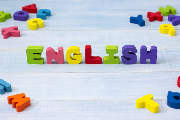 Colorful english word wooden on blue wooden background. english language learning concept Premium Photo