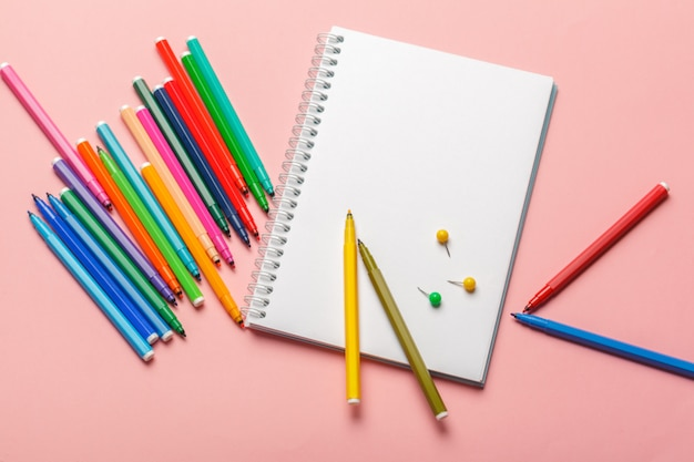 Colorful felt tip pens with blank notepad paper on pink pastel background Premium Photo