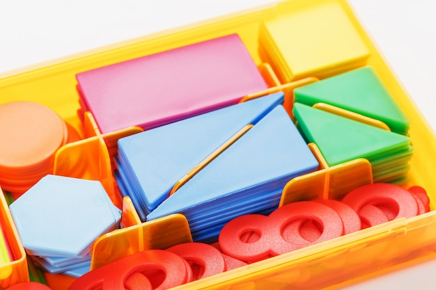 Colorful figures and numbers for children in a box. a tool for developing children's thinking. Premium Photo