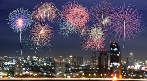 Colorful fireworks on blur city skyline background at night Premium Photo
