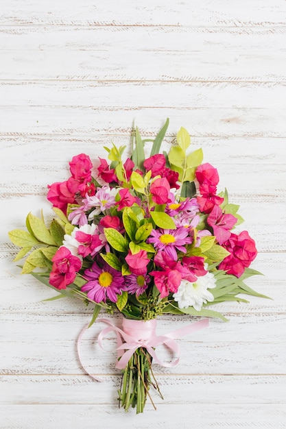 Colorful flower bouquet tied with pink ribbon on wooden desk Free Photo