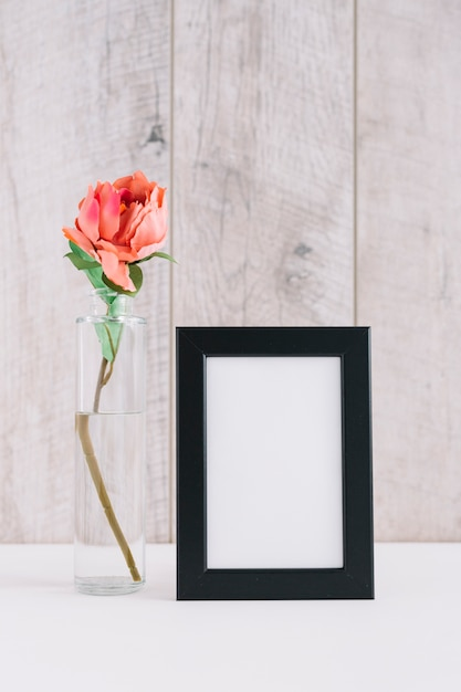 Colorful flower in vase near blank picture frame on table Free Photo