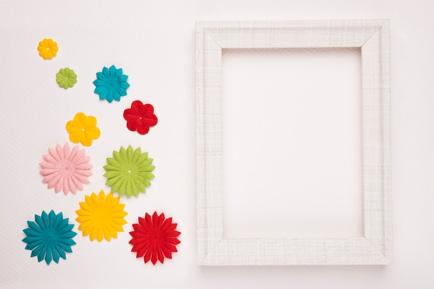 Colorful flowers near the white wooden frame isolated on background Free Photo