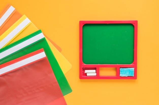 Colorful folders and small green chalkboard Free Photo
