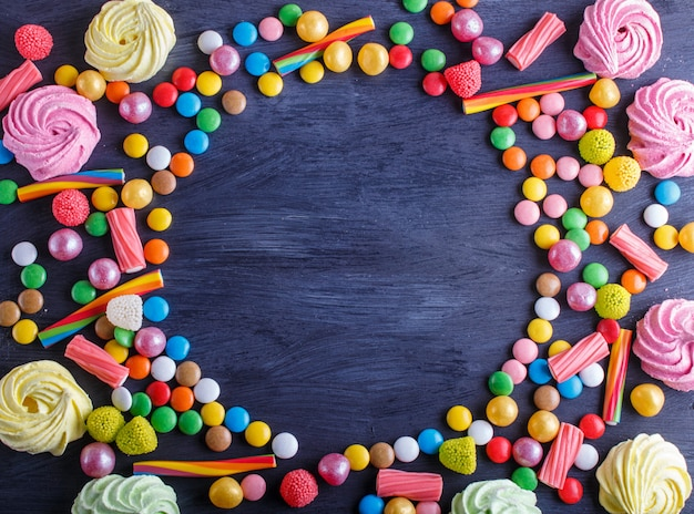 Colorful frame of multicolored candies on black wooden background Premium Photo