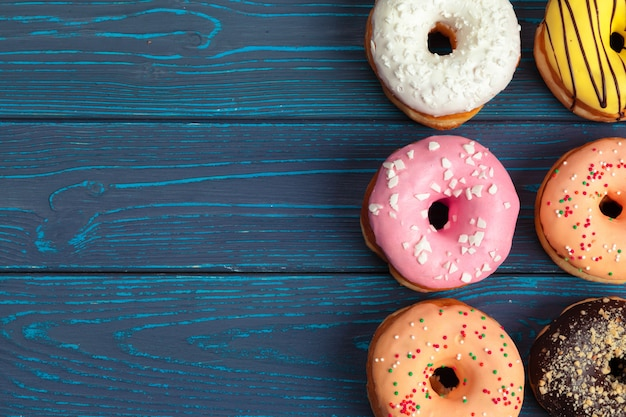 Colorful fresh donuts on dark blue wooden background Premium Photo