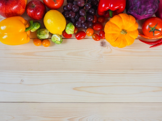 Colorful fresh fruits and vegetables on wood background ...