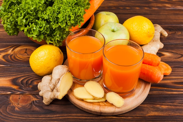 Colorful fruit and vegetables with juice on table Free Photo