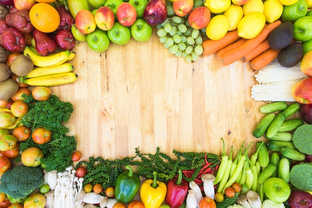 Colorful fruits and vegetables on plank background ...