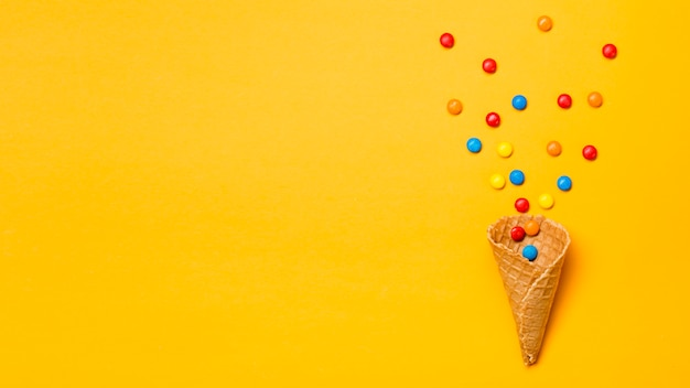 Colorful gems spilled from waffle cone on yellow backdrop Free Photo