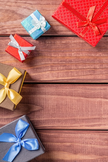 Colorful gift boxes on dark wood background Premium Photo