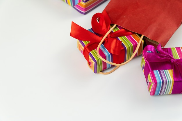 Colorful gifts coming out of paper bag Free Photo